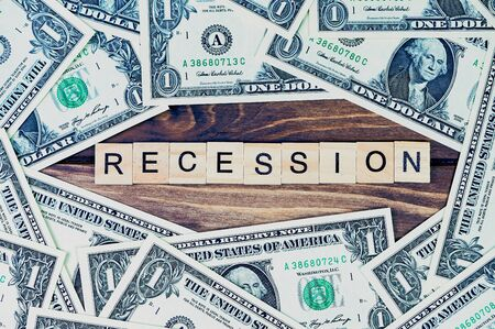 the word recession in the middle on wooden background, around are lying one Dollar bills