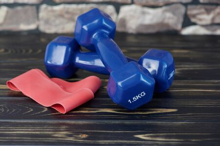 red elastic exercise band beside blue dumbbells on wooden surface