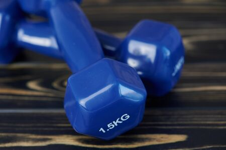 close up of blue hand weights on wooden surface Stock Photo