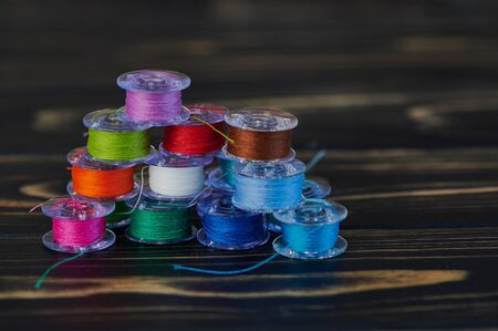 macro of colored cotton thread on yarn bobbins on brown wooden background in a stack