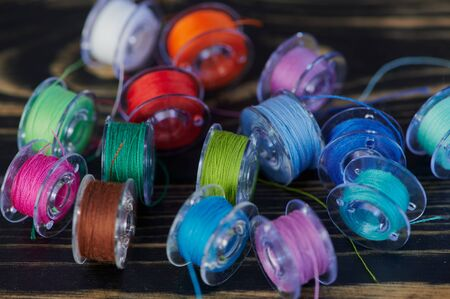 macro of multi colored cotton thread on yarn bobbins on wooden table