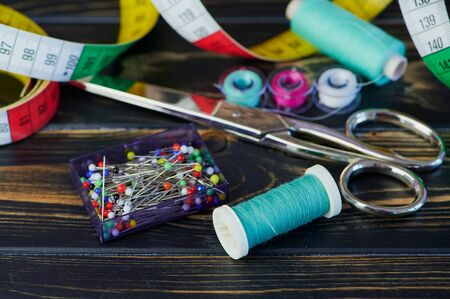 macro color photo of different sewing tools like scissors and sewing thread on wooden table