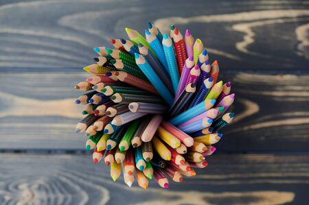 colored pencils in a pencil cup on wooden table, close up photo, view from above