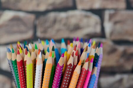 colored pencils, close up photo in front of a blurred wall background