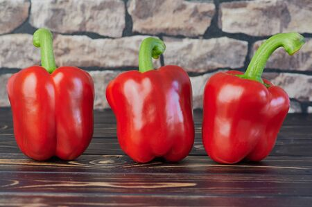 three red peppers on a wooden table in front of a blurred wall Stock Photo