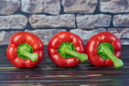 three red peppers lying on a wooden table in front of a blurred wall