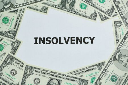 word insolvency printed on a white paper, around are lying Dollar bills Stock Photo