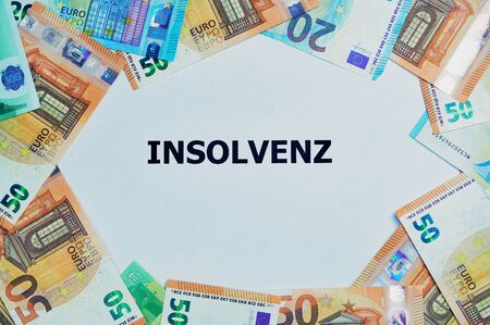 the German word for insolvency is printed on a white paper, around are lying a lot of different Euro banknotes
