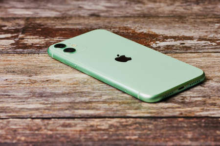 Mainz, Germany - October 28, 2019: New green Apple iPhone 11 on a wooden background. The latest model of Apple mobile phones.