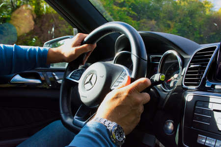 Mainz, Germany - October 03, 2019: Hands of a man in a Mercedes GLE 500 cockpit while driving.