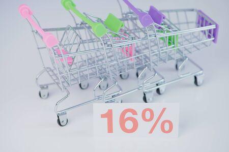 Einkaufswagen Miniatur mit einem 16 % Schild als Darstellung der Umsatzsteuersenkung in Deutschland aufgrund von Covid 19 Stock fotó