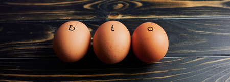 the German word BIO which means in English ORGANIC stamped on three eggs on wooden surface, web banner size