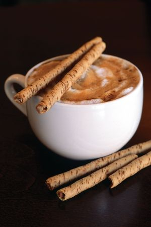Hot cappucino with chocolate sticks on a dark wood table.