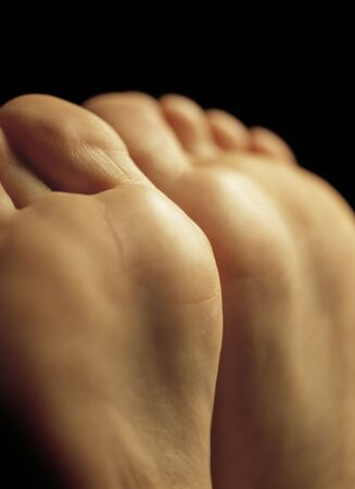 podiatrist: Two female feet waiting for a massage. Very shallow depth-of-field, focus is in the middle. Stock Photo