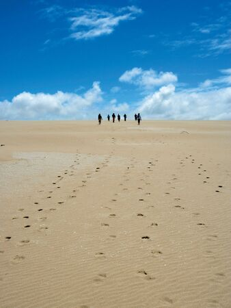 badland: Group of people walking on sand dunes in Southern Australia.