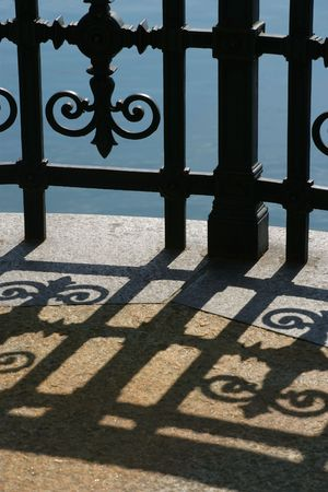 balcony: Shadow of a fence that curves around a river in Zurich.