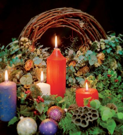 christmastide: Christmas candles, decorations, holly, and wreath.  Sharp in the centre and blurred around the edges. Stock Photo