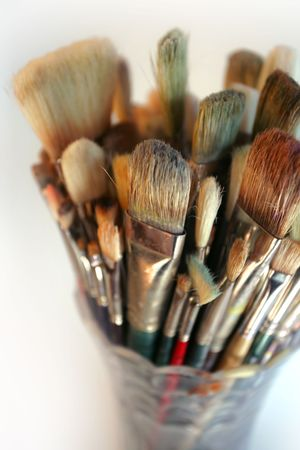 daubs: A very shallow depth-of-field image of used paintbrushes stacked in a glass vase. Focus is on the front brushes.