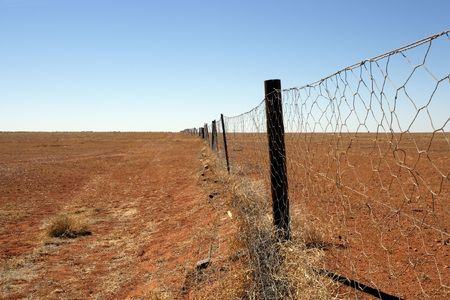 tucker: An image of the Dingoe fence in the Australian Outback.  The fence is 9600 kilometres long and spans the entire country, keeping the dingoes out of the south where the sheep graze.