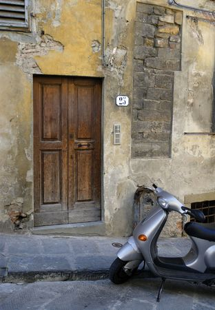 Scooter waiting outside the wooden door of a residence in Florence, Italy. photo