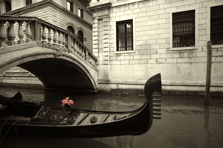 Pink flowers waiting on a rain covered gondola in Venice, Italy. photo