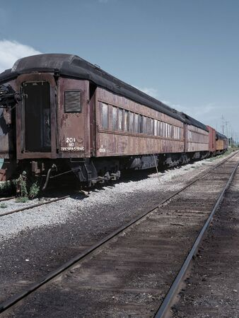rotting: An old passenger train rotting away in a rail yard.
