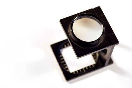 Shallow depth of field image of a Printers loupe on white background.