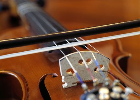 fiddles: Closeup of a bow on the strings of a violin. Stock Photo
