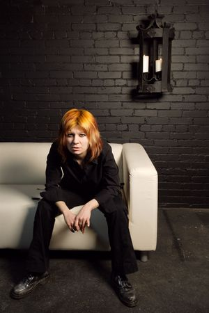 Orange-haired attitude girl sitting alone on a couch. Stock Photo - 819104