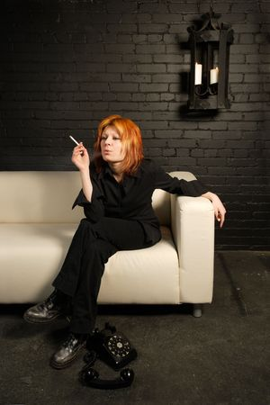 Female with dyed orange hair sitting on a couch smoking a cigarette. Stock Photo - 865455