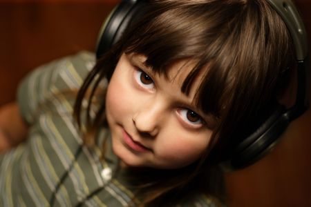 Adorable five year old wearing headphones. Stock Photo