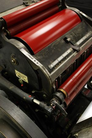 numbering: Image of an old windmill printing press  die cutter  numbering machine, with bright red ink on its rollers.