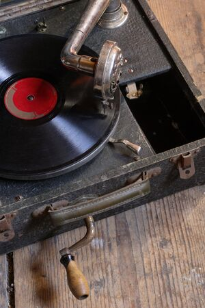 attic: An antique box record player with crank, sitting on the attic floor.