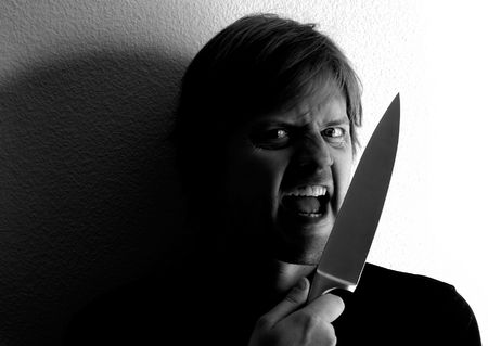 insane insanity: Crazy fellow wielding a knife.  Harsh lighting and shadows for more dramatic effect. Stock Photo