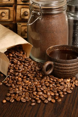 Image of roasted coffee beans, coffee cup, and ground beans on a wooden table.