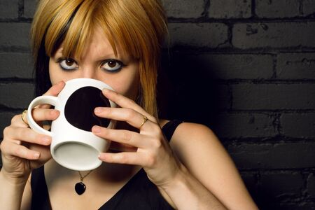 Female drinking coffee against the black brick wall of a urban café. Stock Photo - 1374078