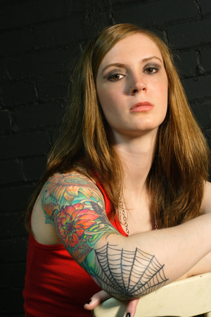 arm tattoo: A young female with serious stare and arm tattoo. Stock Photo