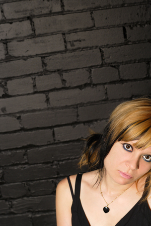 A bored Cristine leaning against a black brick wall. Lots of area for text. Stock Photo - 1425908