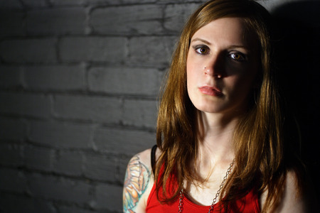 arm tattoo: Image of a serious girl with upper arm tattoo.  Harsh lighting for more dramatic effect.