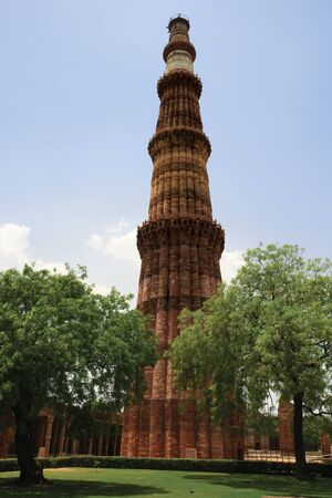 delhi: Looking through the trees at Qutub Minar, the red sandstone tower in Delhi, India, covered with beautiful carvings