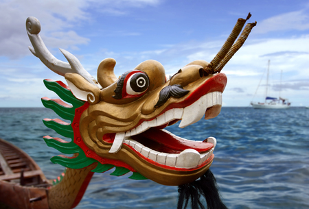 chinese dragon: An empty Chinese Dragon boat waiting in the water. Focus is on the dragon eye. Stock Photo
