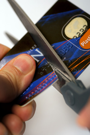 Macro image of scissors cutting through a credit card.  Logos are fake and numbers have been changed.  Colours of the card have been altered also.