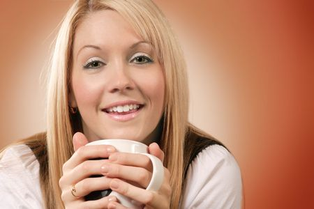 Happy and smiling female drinking coffee in an urban caf�. photo
