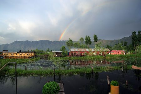 appears: Houseboats in Srinigar, Kashmir (India) - after a light rain a rainbow appears in the distance with mountains as the backdrop.