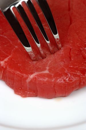 Dinner plate with a fork piercing raw red meat. photo