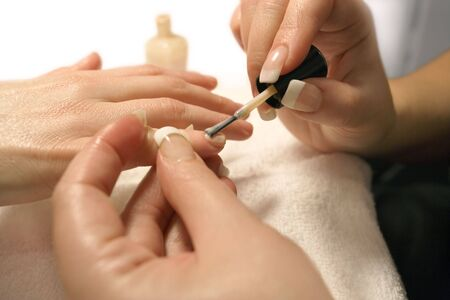 french manicure sexy woman: A manicurist applying nail polish during a manicure.