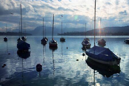 lens flare: Gruppo di barche a vela ancorate vicino alla banchina, come il sole inizia a impostare. Lens flare visibile. Prese a Lucerna, Svizzera.
