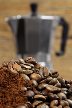 stovetop: Image of an Italian Moka Express stovetop coffee maker behind coffee beans and grinds.  Shallow depth of field - focus is on top layer of beans.