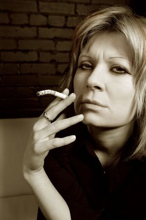Image of an attractive female smoking a cigarette in a dark lounge. Stock Photo - 2625274