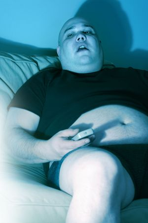 Lazy overweight male sitting on a couch watching television.  Harsh blue lighting from television with slow shutter speed to create TV watching atmosphere. Selective focus on the eyes.